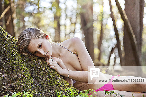 Sad woman in bikini leaning on tree