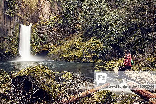 Wanderer betrachtet Wasserfall  während er auf einem Felsen im Wald sitzt