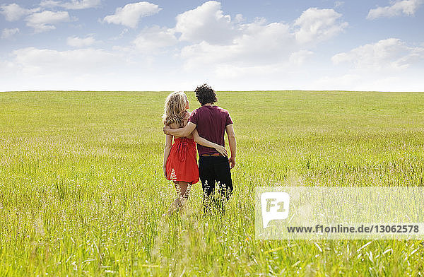 Rear view of couple walking on grassy field against sky