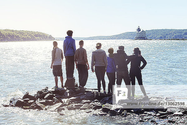 Rear view of friends standing on rocks in river against clear sky