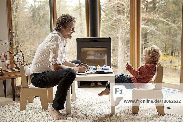Glückliche Vater und Sohn sitzen zu Hause auf Stühlen
