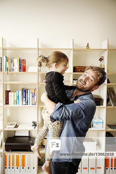 Vater trägt Tochter  während er zu Hause am Regal steht