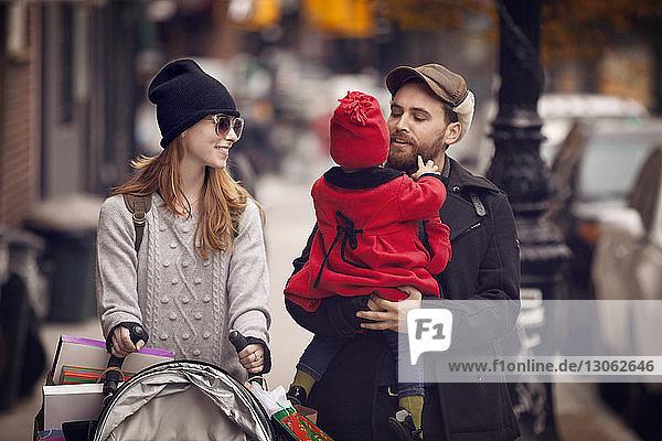 Vater trägt Tochter  während er mit Frau auf der Straße geht