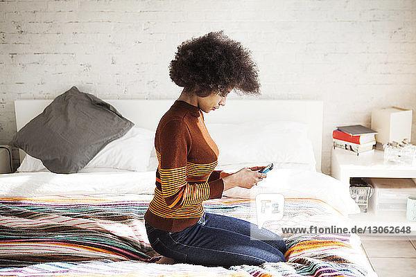 Seitenansicht einer Frau  die ein Smartphone benutzt  während sie zu Hause auf dem Bett kniet