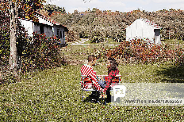 Paar  das sich an den Händen hält und einander anschaut  während es im Hinterhof sitzt