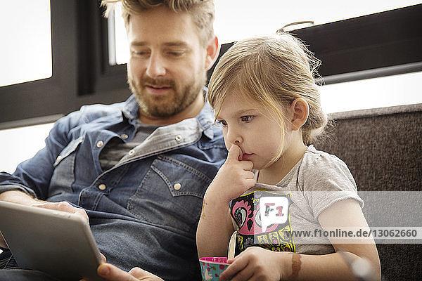 Mädchen sieht Vater am Tablet-Computer an  während sie zu Hause auf dem Sofa sitzt