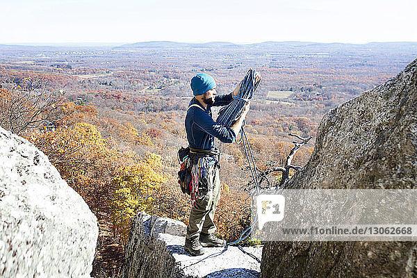 Mann hält Kletterseil  während er am Fels steht