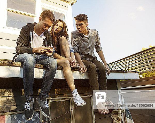 Freunde schauen auf Smartphone  während sie auf dem Dach sitzen