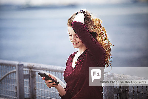 Woman with hand in hair using smart phone against river