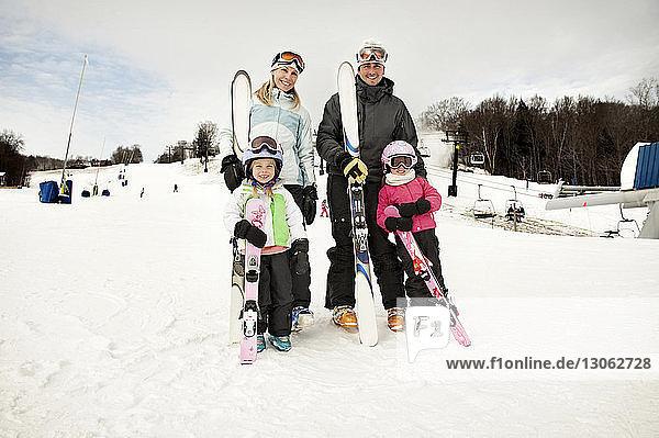 Porträt einer glücklichen Familie  die Skier auf einem schneebedeckten Feld gegen den Himmel hält