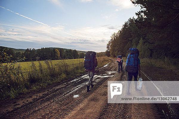 Rückansicht von Freunden  die auf einem Feldweg gegen den Himmel laufen