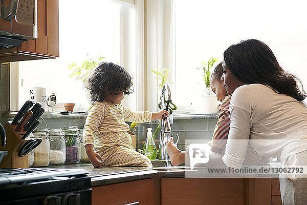 Mutter sieht Kinder an  die zu Hause im Waschbecken Füße waschen