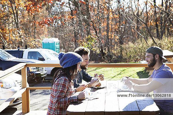 Freunde essen im Restaurant im Freien gegen parkende Autos