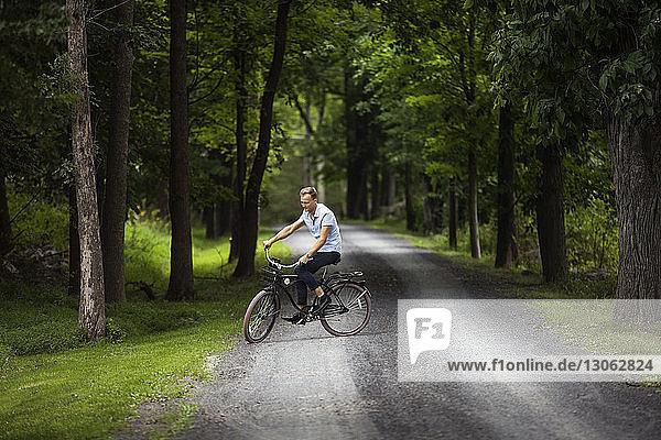 Glücklicher Mann fährt Fahrrad auf Straße im Wald
