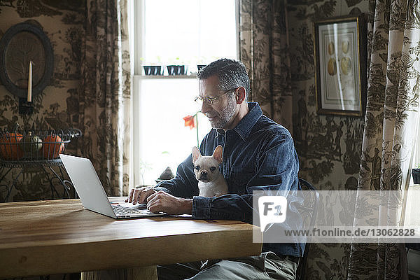 Man using laptop computer while sitting with dog by table at home