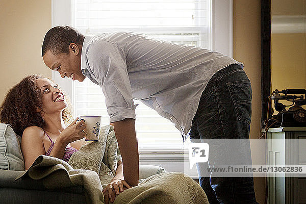 Romantic man leaning on woman at home