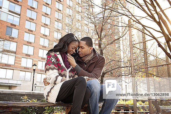Low angle view of young couple sitting on bench against building