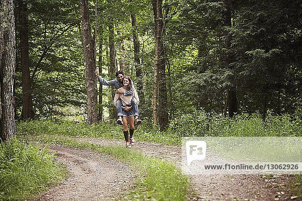 Frau nimmt Mann huckepack  während sie auf Feldweg im Wald geht