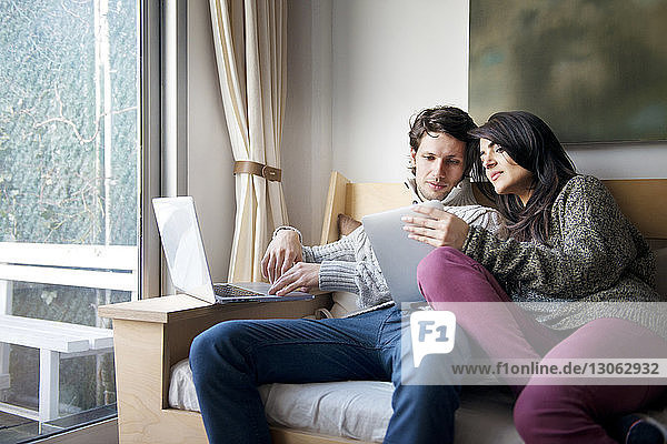 Woman showing digital tablet to boyfriend on sofa at home