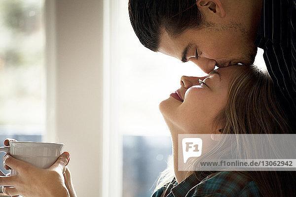 Mann küsst zu Hause seine Freundin auf die Stirn