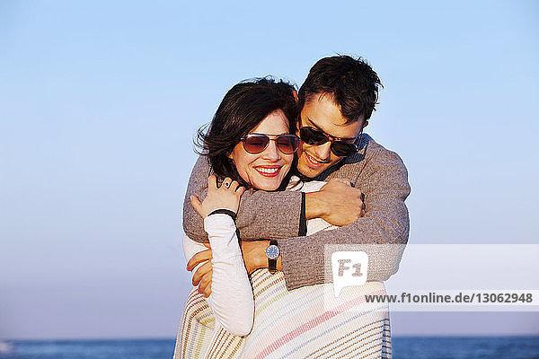 Mann umarmt Frau am Strand bei Sonnenuntergang