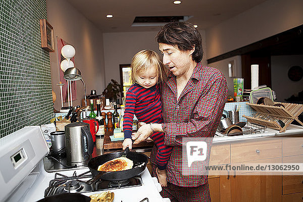 Father and son cooking pancake in kitchen at home