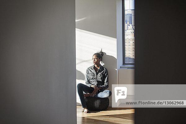 Junge Frau schaut weg  während sie zu Hause sitzt