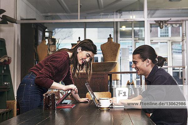 Glückliches Paar schaut auf Laptop-Computer  während es im Bekleidungsgeschäft sitzt