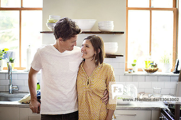 Happy couple looking at each other while standing in kitchen