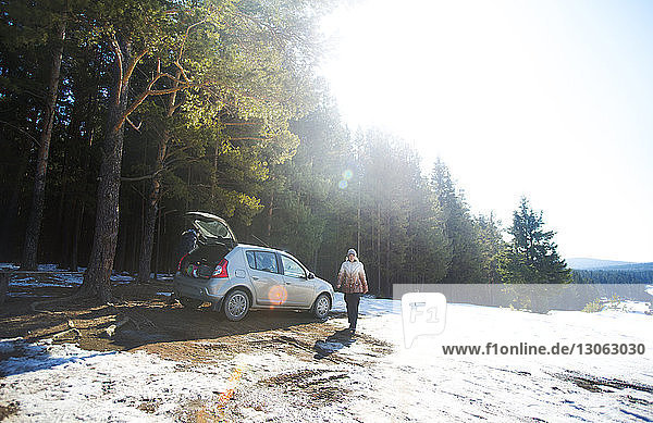 Friends by car in forest on sunny day during winter