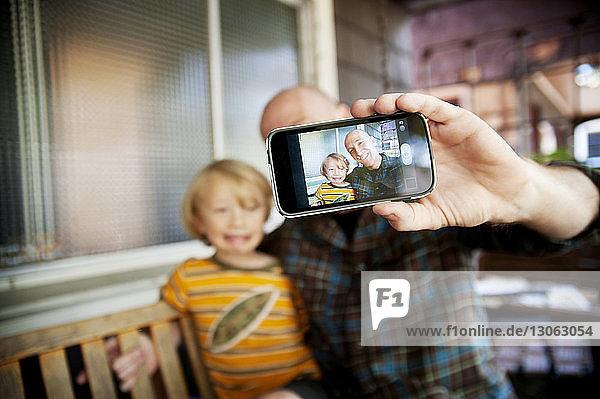 Glückliche Familie  die zu Hause auf der Schaukel sitzt