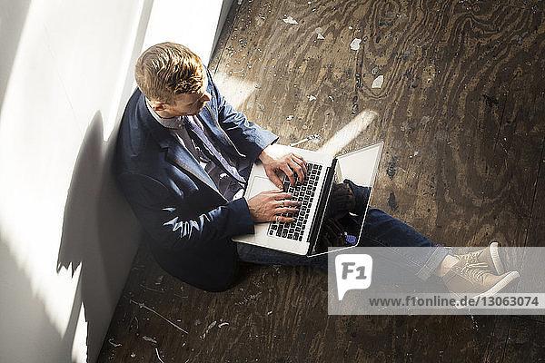 Hochwinkelansicht eines Mannes  der zu Hause einen Laptop benutzt