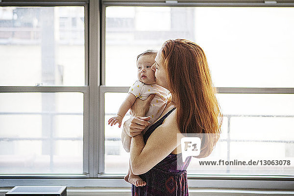 Woman kissing daughter while standing by window at home