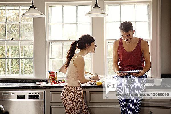 Glückliches Paar benutzt Tablet-Computer beim Kochen in der heimischen Küche