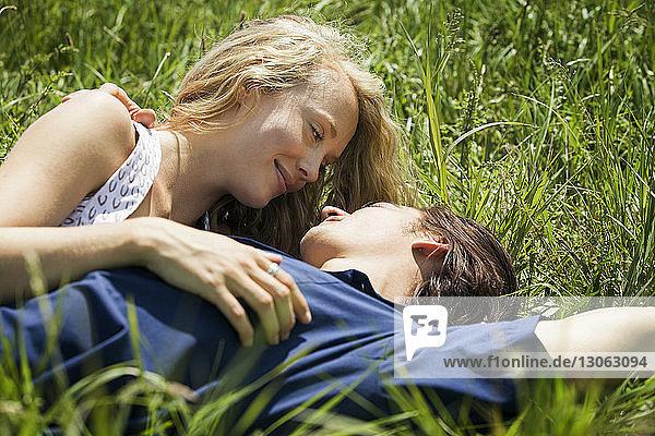 Couple lying on grassy field