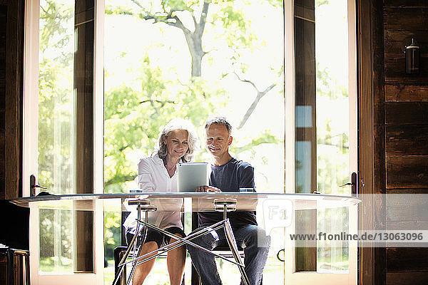 Glückliches älteres Ehepaar mit Tablet-Computer zu Hause sitzend
