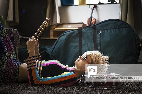 Seitenansicht einer Frau  die zu Hause auf einem Teppich liegt