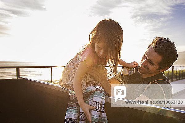 Mann hebt Mädchen bei Sonnenuntergang vom Pick-up gegen den Himmel