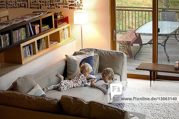 High angle view of siblings playing on sofa at home