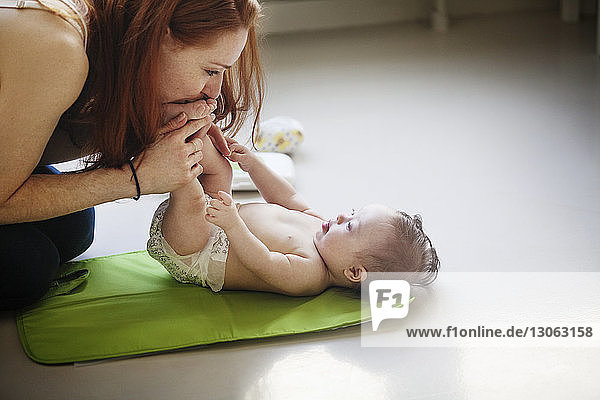 Woman kissing baby girl feet at home