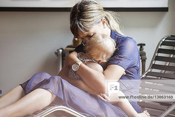 Mutter umarmt Tochter  während sie zu Hause auf einem Liegestuhl sitzt