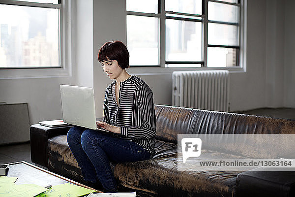 Businesswoman using laptop while sitting on sofa at creative office