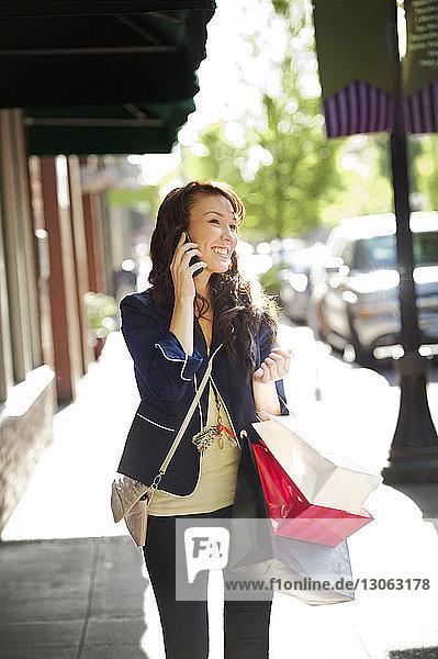 Glückliche Frau spricht mit Smartphone  während sie auf einem Fußweg geht