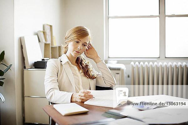 Frau liest Buch  während sie im Büro am Schreibtisch sitzt