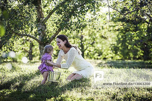 Frau hält Tochter mit Eimer im Obstgarten