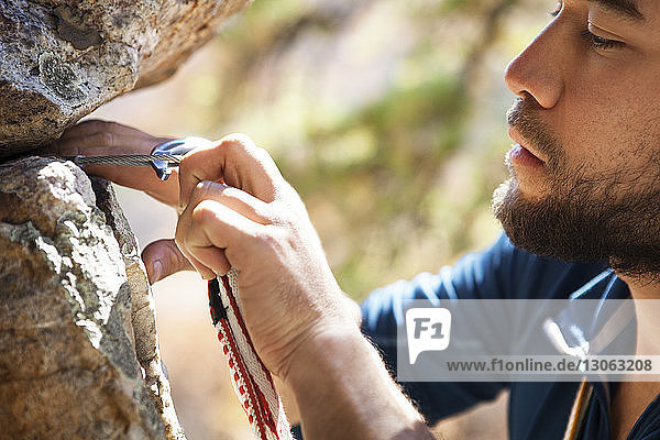 Beschnittenes Bild eines Bergsteigers  der Karabiner an Felsen befestigt