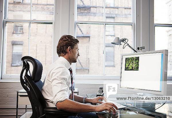 Seitenansicht eines Geschäftsmannes  der im Büro am Desktop-Computer arbeitet