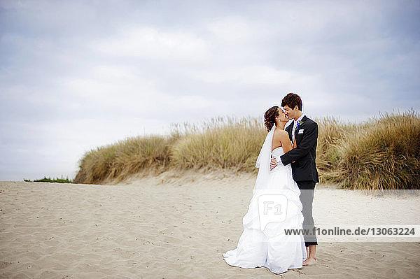 Pärchen küsst sich am Strand stehend gegen den Himmel