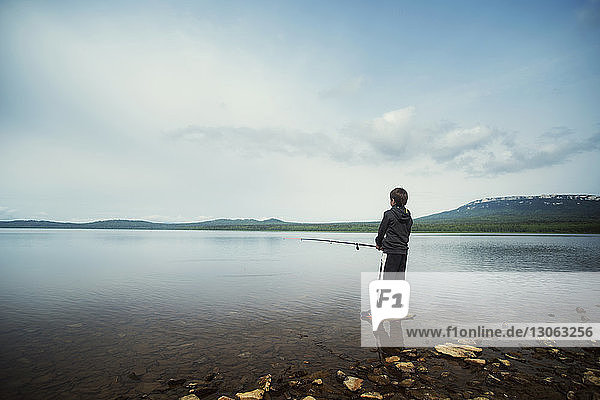 Rear view of boy fishing at lake against sky