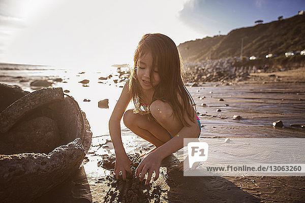 Mädchen spielt bei Sonnenuntergang im Sand am Strand